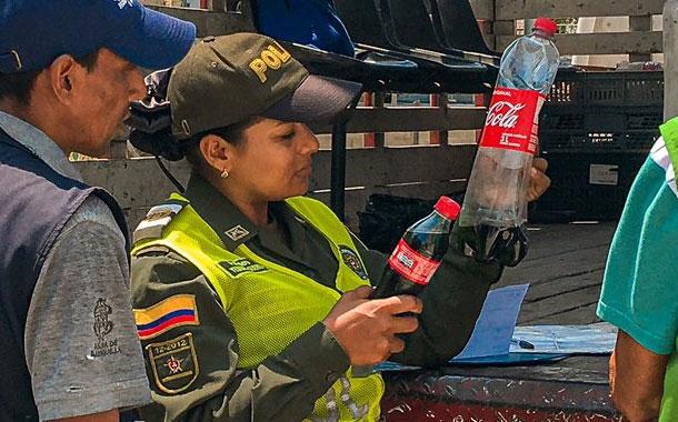Captan a vendedor ambulante en Colombia rellenando botellas de Coca-Cola